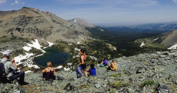 The class at Firebrand Pass on eastern side of Glacier National Park watching a moose wade in the lake and big horn sheep traverse the mountainside.