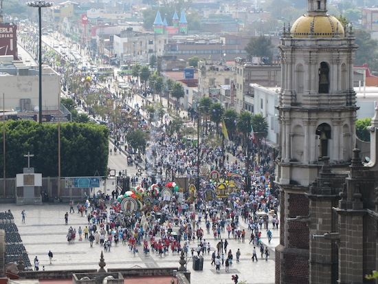 One of many processions to the Basilica with pilgrim groups carrying large floats of Our Lady of Guadalupe.