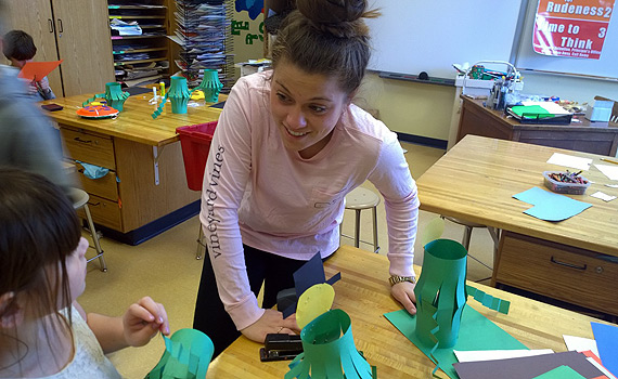 Colgate student volunteer helps Madison Central 4th grader with a craft project.