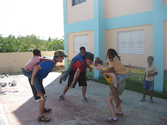 Three Colgate students playing with Dominican children in a school play yard