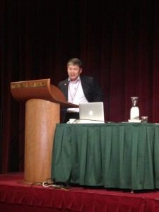 Professor John Palmer speaking at a podium