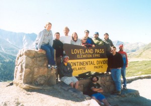 Students pose for a picture around the Loveland Pass sign