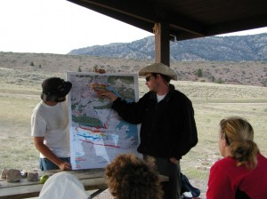 Student in cowboy hat points at topographical map