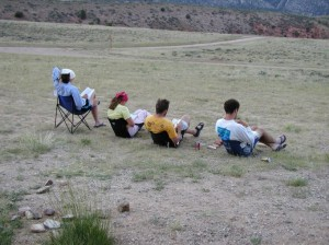 Students sit in camping chairs, working