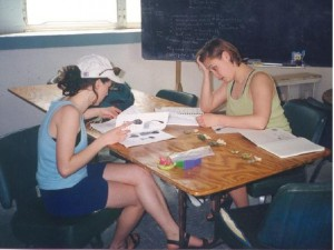 Two students review papers at a table.