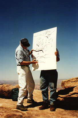 Faculty members draw on a whiteboard outdoors