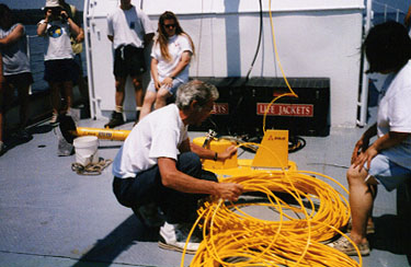 Faculty member prepares a sonar device on the deck of a boat