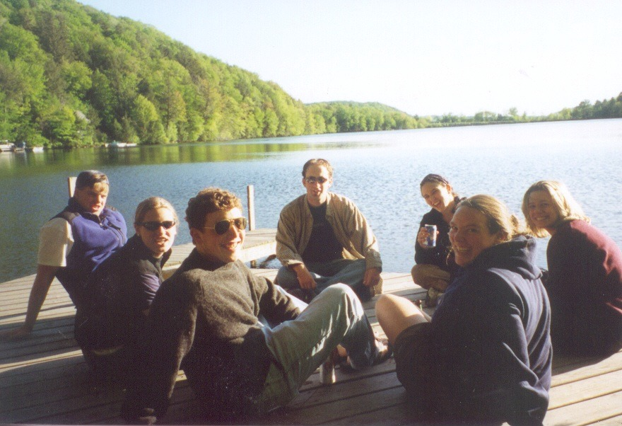Students sit on a group on a dock at a lake