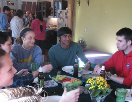 In the foreground (left to right) Jen Godbout, Emily Butler, Katherine Schultz, Anay Shah, and Sam Brenman share a laugh, while back in the kitchen, Profs. Martin Wong and Connie Soja converse with Sarah Katz, Avalon Bunge, Maggie McGuire, and Giuliana Kafaf