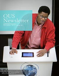 Cover of the November 2013 newsletter in which a student speaks in at a podium