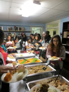Students serving food at a family dinner in La Casa