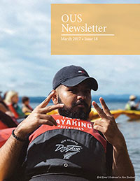 Newsletter cover featuring a male student in a baseball cap giving the peace sign while kayaking