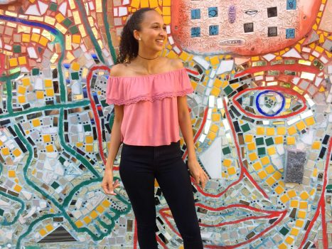 DJonita Cottrell looks off to the right, smiling, as she stands in front of a multi-colored glass mosaic