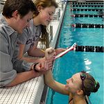 Two students check the pulse rate of a female swimmer in the pool