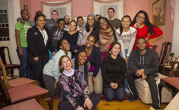 Students and and Mary Moran pose for a photo in her home