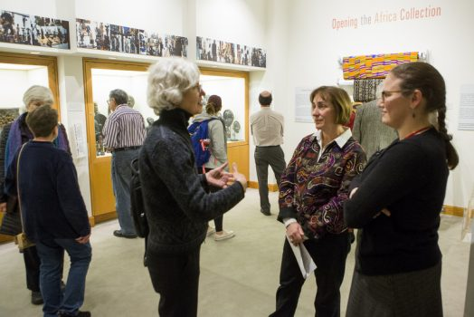 "Professor Moran and Longyear Curator Christy DeLair speak with a visitor to the ""Opening the Africa Collection"" exhibit"