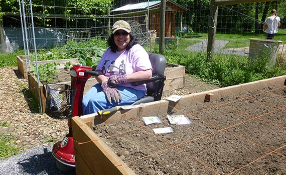 Professor Aisha Musa working in the Colgate Community Garden