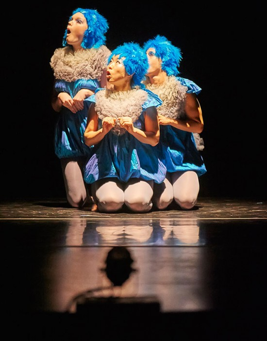 Three dancers in blue feathers on stage