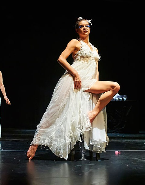 Dancer in white dress on stool on stage