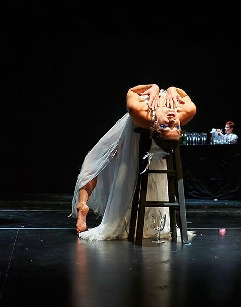 Dancer on stage leans backward over stool