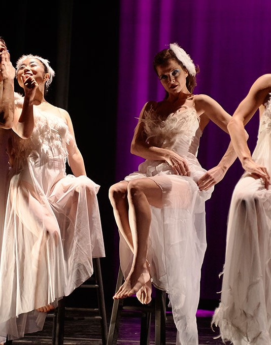 Four dancers in white dresses share a drink on stage