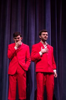Students onstage in red suits