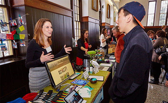 Amanda Brown '15 (left) talks with a student at  Entrepreneur Weekend in April.