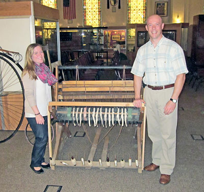 Tess Christianson and Brian Howard with one of the many objects from the exhibit on the history of the Oneida County Historical Society.