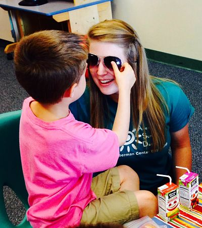 Lauren Kasparson '15 with a camper at the Awesome Summer Days Camp.
