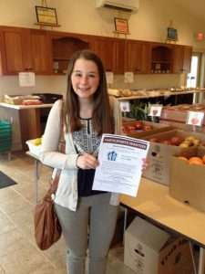 Emily Rooney '17 at Pathfinder Village's weekly produce market