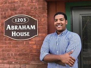 Zakaria Chakrani '18 posing next to Abraham House sign
