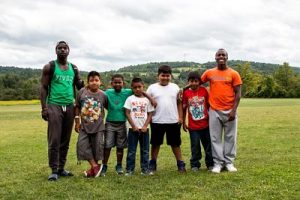 Mykel and a fellow counselor pose with children from the summer camp in a field