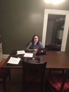 Elizabeth sits at a desk, on her laptop while working on creating marketing content